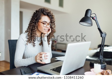Beautiful business woman with curly hair working casually, drinks coffee / tea