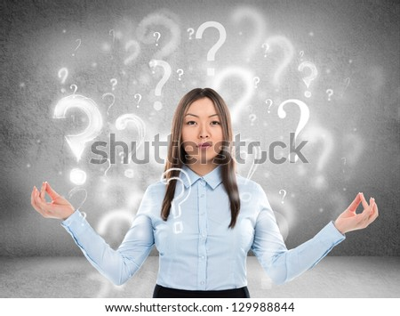 Beautiful business woman with question marks above her head