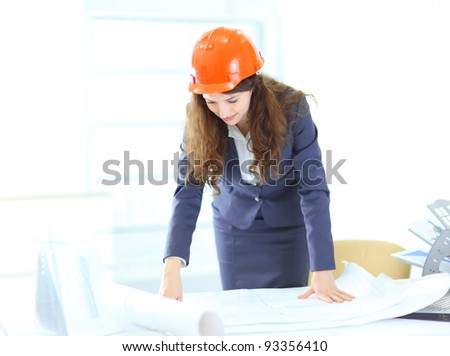 Beautiful businesswoman, an engineer with the work plan, standing in the office.