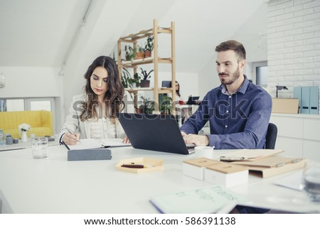 Beautiful businesswoman and handsome businessman working together at office desk. #586391138