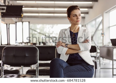 Beautiful businesswoman at the co-working is thinking. Blurred background. Film effect. Open space #684781528