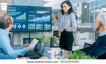 Beautiful Businesswoman Gives Report/ Presentation to Her Business Colleagues in the Conference Room, She Shows Graphics, Pie Charts and Company's Growth on the Wall TV. #1031044342