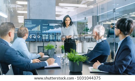 Beautiful Businesswoman Gives Report/ Presentation to Her Business Colleagues in the Conference Room, She Shows Graphics, Pie Charts and Company's Growth on the Wall TV. #1031044375