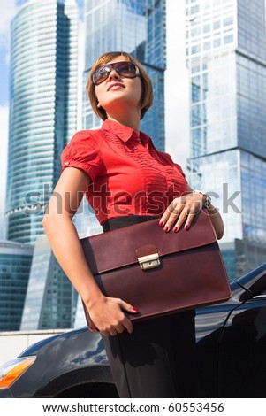 Beautiful businesswoman holding a briefcase near the car on a background of skyscrapers - stock photo