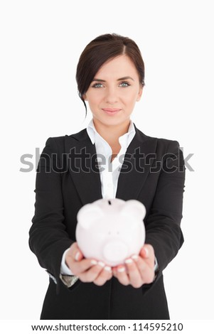 Beautiful businesswoman holding a piggy-bank against white background