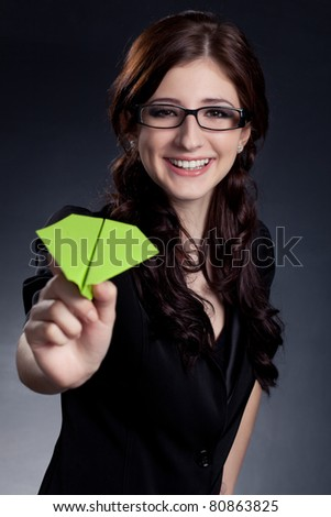 beautiful businesswoman  holding paper plane over black background