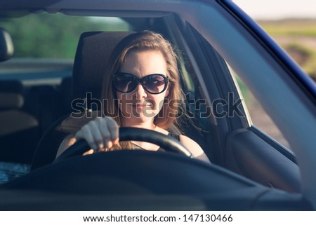 Beautiful businesswoman in sunglasses driving her car