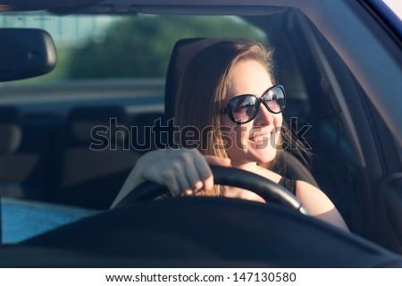 Beautiful businesswoman in sunglasses driving her car