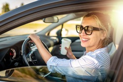 Beautiful businesswoman is sitting at steering wheel of her car. She is drinking coffee and smiling. The lady is looking at the camera happily