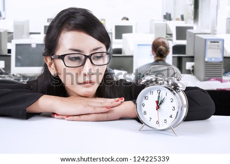 Beautiful businesswoman looking at a clock