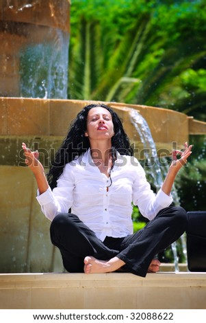 beautiful businesswoman practicing yoga  outdoors, meditating on the edge of a fountain