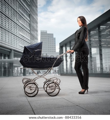 Beautiful businesswoman pushing a pram with office buildings in the background