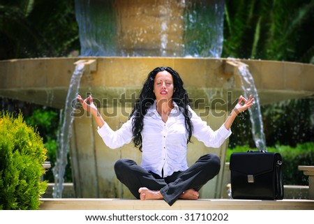 beautiful businesswoman relaxing outdoors, meditating on the edge of a fountain