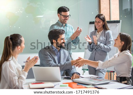 Beautiful businesswoman shaking hands with businessman while their colleagues clapping hands and celebrating successful business partnership in the office