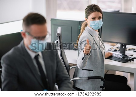 Beautiful businesswoman showing thumbs up. Businesswoman with medical mask.