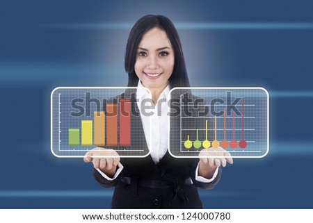Beautiful businesswoman shows two virtual diagrams with upward movement