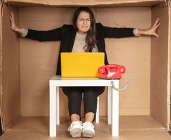 beautiful businesswoman sits in a tight paper office, needs more space, pushes the walls