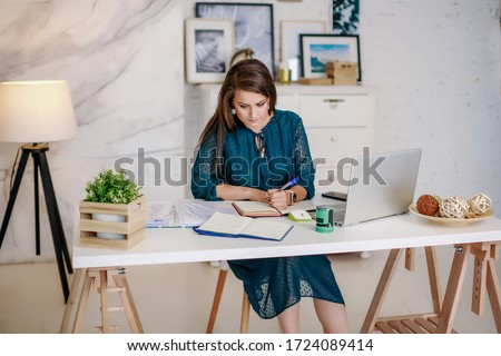 Beautiful businesswoman sits in an office in an office at a table, fills out a contract or financial report. Image with selective focus Foto d'archivio ©