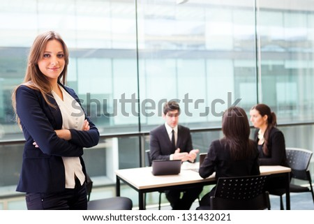 Beautiful businesswoman smiling with his colleagues behind