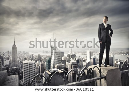 Beautiful businesswoman standing on the rooftop of a skyscraper - stock photo
