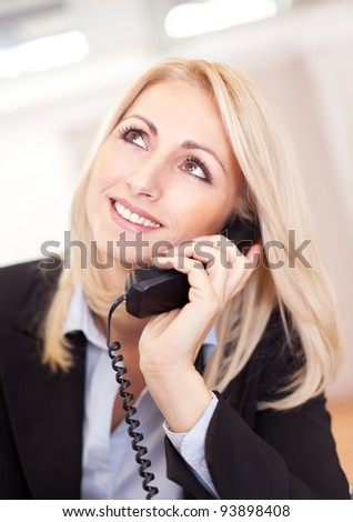 Beautiful businesswoman talking on the phone in the office - stock photo