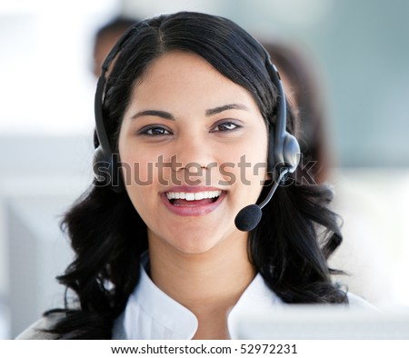 Beautiful businesswoman wearing a headset to talk with customer in the office