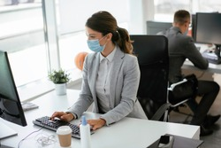 Beautiful businesswoman with medical mask working in office. Covid-19 concept.