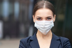 Beautiful businesswoman, young woman, in medical protective mask on her face, in formal jacket standing outdoors, looking at camera. Coronavirus, virus, epidemic, pandemic covid-19 concept