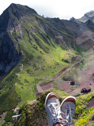 Beautiful cable car ride, sneakers on the background of a mountain landscape, first-person photo. beautiful landscape, Infrastructure for traveling in the mountains. Chair lift.
