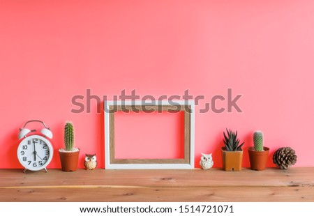 Beautiful  cactus,blank  wooden  picture  frame,alarm  clock,simulated  owl  and  pine  cone  on  wood  table  with  pink  background