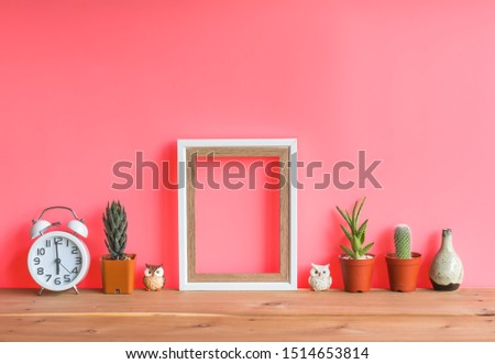 Beautiful  cactus,blank  wooden  picture  frame,simulated  owl  and  alarm  clock  on  wood  table  with  pink  background