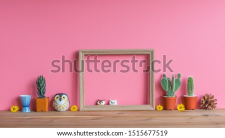 Beautiful  cactus,blank  wooden  picture  frame,simulated  owls  and  pine  cone  on  wood  table  with  pink  background