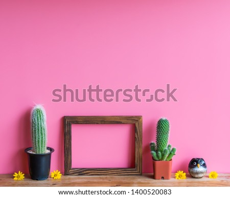 Beautiful  cactus,wooden  picture  frame  and  simulated  owl  on  pink  background