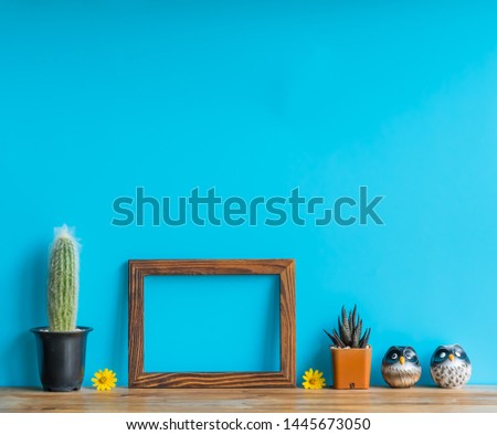 Beautiful  cactus,wooden  picture  frame  and  simulated  owl  on  wood  table  with  blue  background
