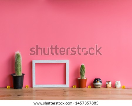 Beautiful  cactus,wooden  picture  frame  and  simulated  owl  on  wood  table  with  pink  background