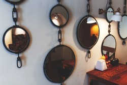 Beautiful cafe interior, wall decorated with various mirrors.