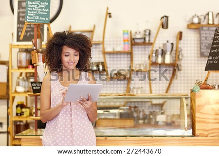 Beautiful cafe owner running her small business with the help of a digital tablet while standing near the counter of her coffee shop