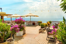 Beautiful cafe with red flowers in Antalya. Outdoor restaurant, turkey, summer vacation