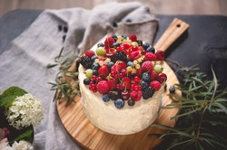 Beautiful cake covered with icing cream, summer berries on the top. Style and food photography