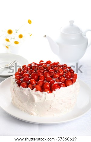 beautiful cake with strawberries and cream on white isolated background