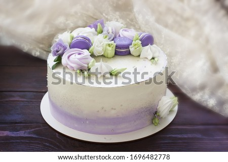 Beautiful cakes. Cake with flowers, purple macaroons and meringues on wooden board. Wedding cake, birthday cake, Mother's day, 8 march, womens day, cake with macaroons