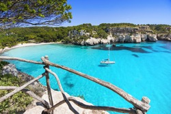 Beautiful Cala Macarella beach, Menorca island, Spain. Sailing boat in a bay. Summer fun, enjoying life, yachting, travel and active lifestyle concept