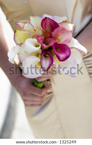 beautiful calla lillies on silk dress with hands wedding bouquet detail