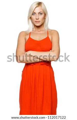 Beautiful calm young woman standing with her hands folded against white background