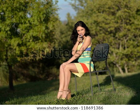 Beautiful calm young woman with glass of red wine outdoor at evening light