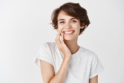 Beautiful candid woman with short hair and without makeup, touching clean facial skin and smiling, standing in t-shirt on white background.