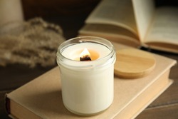 Beautiful candle with wooden wick on book