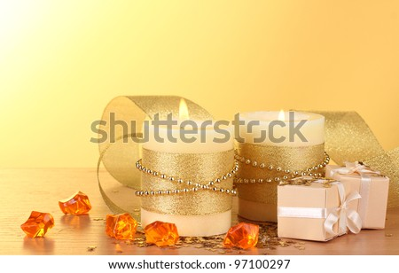 Beautiful candles and gifts on wooden table on yellow background