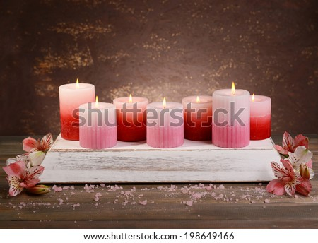 Beautiful candles with flowers on table on brown background