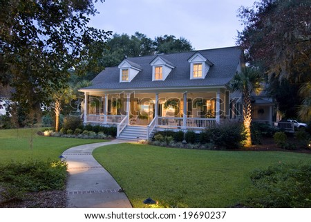 beautiful cape cod house lit up at twilight